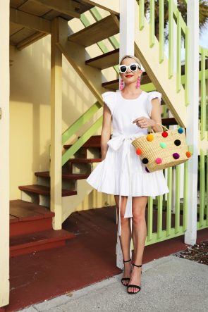 blair-eadie-atlantic-pacific-travel-inspo-outfit-white-dress-rainbow-pom-poms